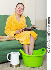 Smiling blonde taking foot bath and reading book