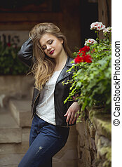 Smiling blonde woman dressed in stylish clothes near the flowers