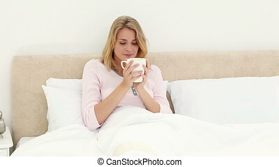 Smiling blonde woman drinking a tea