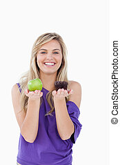 Smiling blonde woman hesitating between a muffin and an apple