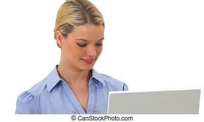 Smiling blonde woman holding a laptop against a white...