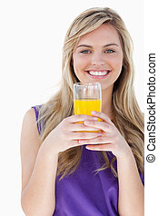 Smiling blonde woman holding an orange juice