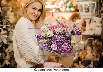 smiling blonde woman holding beautiful bouquet of variety purple flowers