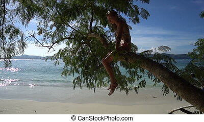 Smiling blonde woman in bikini sitting on a tree branch isolated on a beach