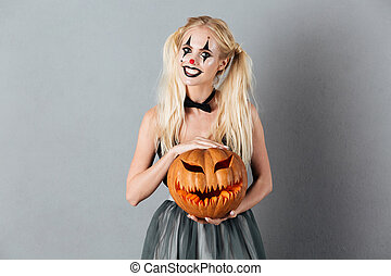 Smiling blonde woman in halloween clown make-up