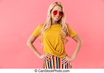 Smiling blonde woman in sunglasses with arms on hips
