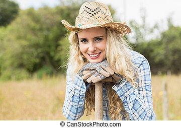 Smiling blonde woman leaning on a shovel