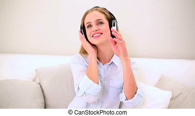 Smiling blonde woman listening musi