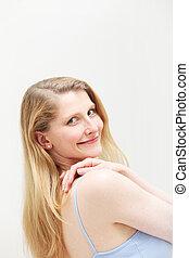 Smiling blonde woman looking over her shoulder