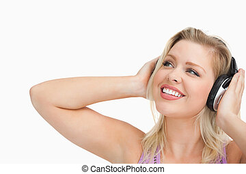 Smiling blonde woman looking up while listening to music