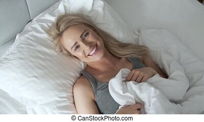 Smiling blonde woman lying in her bed in bright bedroom...
