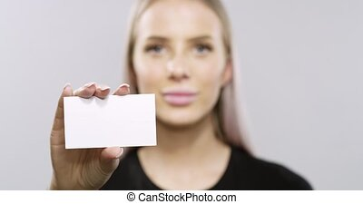 Smiling blonde woman model holding a corporate card