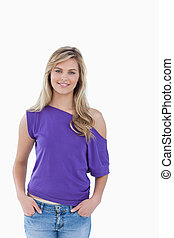 Smiling blonde woman placing her hands in her pockets