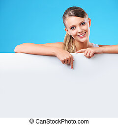 Smiling blonde woman pointing at copyspace