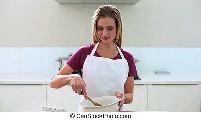 Smiling blonde woman preparing cake