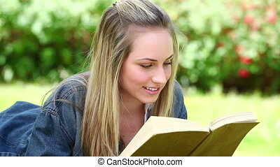 Smiling blonde woman reading a book