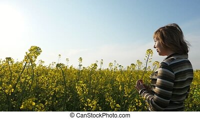 Smiling blonde woman standing in a rapeseed field at...
