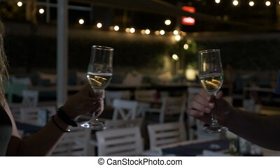 Smiling blonde woman toasting a glass of champagne with...