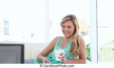 Smiling blonde woman watching the television