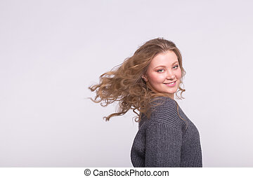 Smiling blonde woman with flying hair on white background with copy space