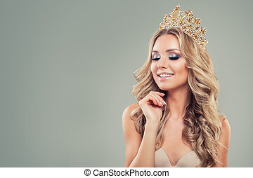 Smiling blonde woman with long curly hair, makeup and gold crown on background with copy space