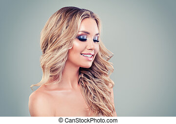 Smiling blonde woman with long curly haircut and makeup on background with copy space