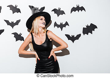 Smiling blonde young woman in witch costume with hat...