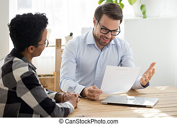 Smiling boss holding cv interviewing black woman