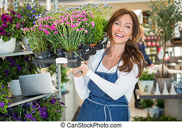 Smiling Botanist Carrying Crate Full Of Flower Plants In Store