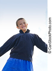smiling boy against blue sky