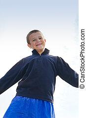 smiling boy against blue sky