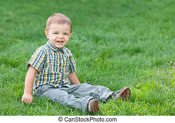 Smiling boy against the green summer grass