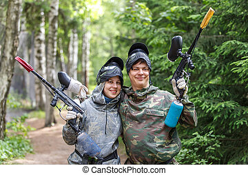 Smiling boy and girl posing with paintball markers outdoors