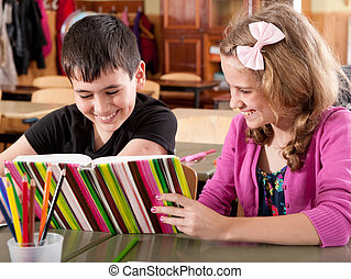 Smiling boy and girl reading book at school