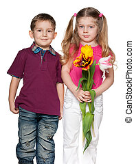 Smiling boy and pretty girl with flowers