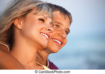 smiling boy and young woman on beach in evening, Looking afar