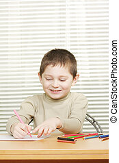 Smiling boy drawing with crayon