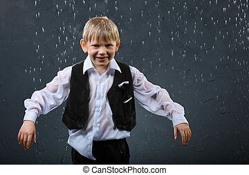 smiling boy dressed in wet white shirt and black vest stands...