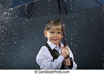 smiling boy dressed in white shirt and black vest standing under umbrella in rain