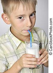 smiling boy drinking milkshake - portrait of smiling boy...