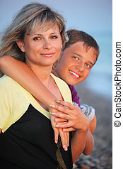 smiling boy embraces young woman on beach in evening