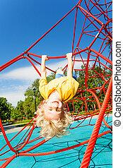Smiling boy hangs upside down on rope of red net