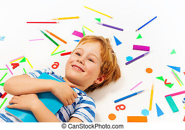 Smiling boy having a rest among heap of stationery