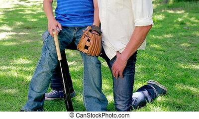 Smiling boy holding a baseball bat and a glove