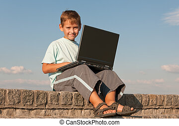 Smiling boy holding a laptop
