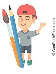 Smiling boy holding big pencil and paintbrush.