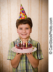 Smiling boy holding birthday cake