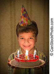 Smiling boy holding birthday cake in hands