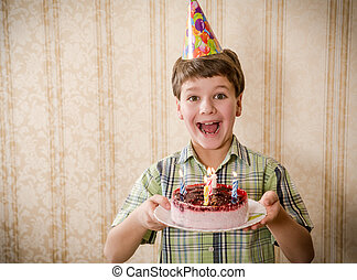 Smiling boy holding birthday cake, space for text