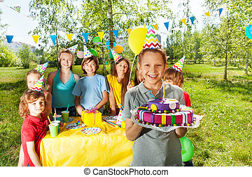 Smiling boy holding birthday cake with candle